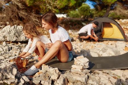 Woman and little girl touching big stone at beach. Standard-Bild - 106357492