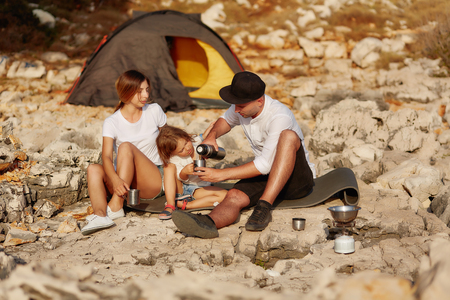 Friendly family, sitting near tent on stone seacoast at daytime. Standard-Bild - 106357493