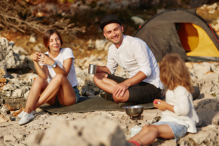 Parents sitting near tent, drinking tea and looking at little daughter. Standard-Bild - 106357494