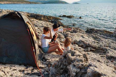 Side view of friendly family sitting near tent at rock beach, admiring sea. Фото со стока