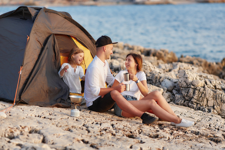 Cheerful family resting on stone shore near tent. Standard-Bild - 106357523