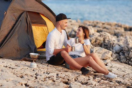 Happy smiling couple sitting face to face at rocky beach on near tent.