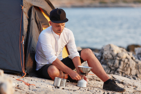 Young man sitting on rocky seashore near tent, setting gas tile. Standard-Bild - 106357529