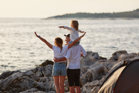 Back view of happy parents with little daughter, sitting on daddy neck. Фото со стока