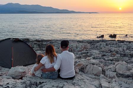 Back view of family, sitting on rock beach, admiring setting sun over sea. Standard-Bild - 106357535