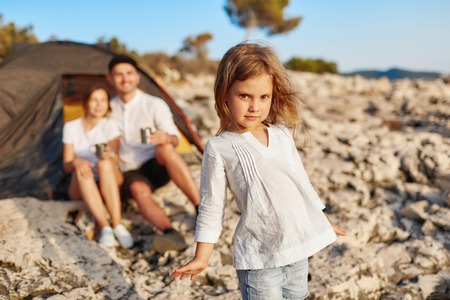Little girl with brown eyes, standing on rocky beach and looking at camera.