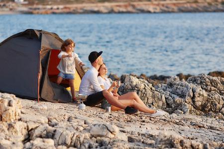 Friendly sincere family resting on rocky beach near tent. Standard-Bild