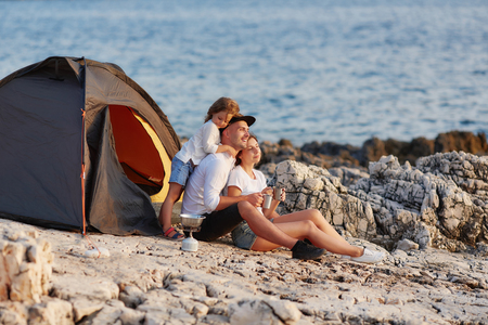 Friendly sincere family resting on rocky beach near tent. Banco de Imagens