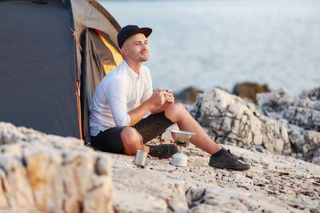 Man sitting with an iron cup on rocky coast of sea.