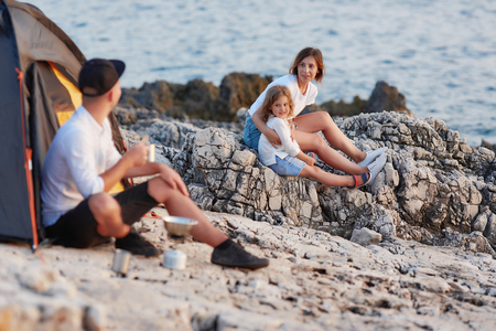 Man sitting on rocky coast looking at his wife and daughter,sitting near. Фото со стока