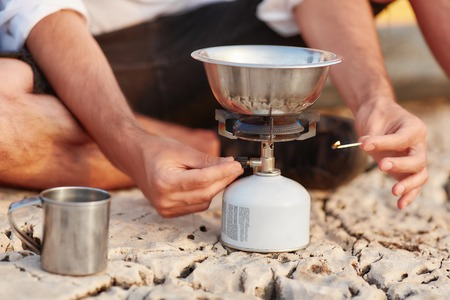 Male hand ignited match at portable gas stove.
