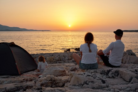 Back view of family, sitting on rock beach, admiring setting sun over sea.