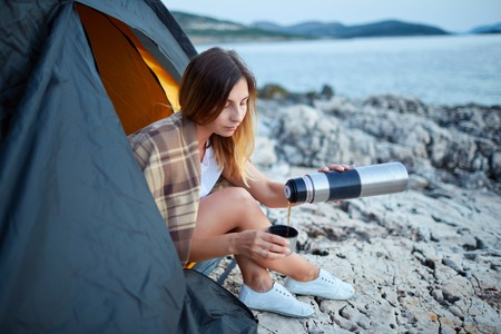 Girl sitting in tent, carefully pouring tea from container into iron cup. Standard-Bild - 122905181