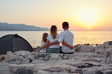 Back view of cute young family, sitting on rock beach near tent and admiring setting sun over sea. Mom, dad and little daughter embracing and having great time together. Concept of friendly family.