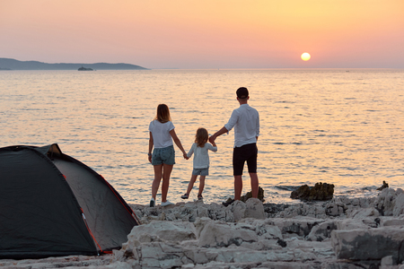 Back view of sweet young family, standing on rock beach near tent and joying setting sun over sea. Mom, dad and little daughter holding hand and having best time together. Concept of friendly family.