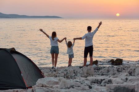 Back view of sweet young family, standing with open hands on rock beach and enjoying setting sun over sea. Mom, dad and little daughter holding hand and having best time together at summer vacation.