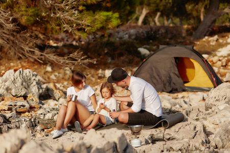 Friendly family, sitting near tent on stone seacoast at daytime. Standard-Bild - 122905187