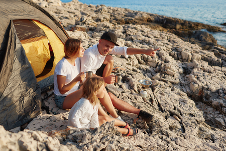 Side view of friendly family sitting near tent at rock beach, admiring sea. Фото со стока
