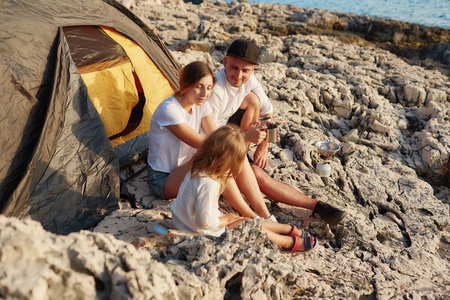 Friendly young family, sitting on ground near tent on stone seacoast.