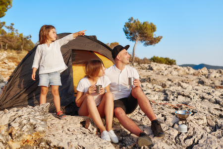 Family sitting near tent at rock beach admiring summer vacation. Фото со стока