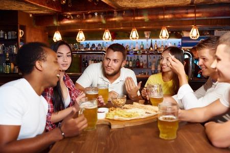 Happy friends group drinking beer at brewery bar restaurant. Standard-Bild