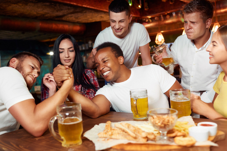 Two playful male friends having arm wrestling challenge at bar.