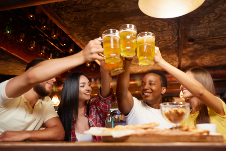 Four boys and two girls having fun together, raising beer above table.