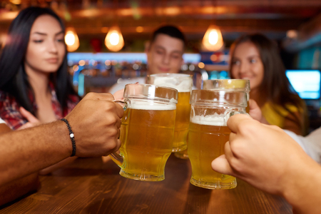 Four friends toasting with glasses of light beer at pub. Banco de Imagens