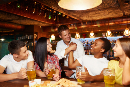 Two men greeting and shaking hands in pub. Standard-Bild - 107927678