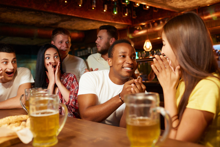 Man surprisingly proposing beautiful girlfriend to marry him in bar.