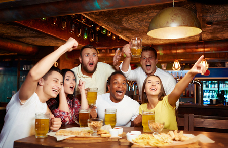 Happy friends having fun in pub watching sport in TV together.