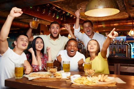 Happy friends having fun in pub watching sport in TV together. Standard-Bild - 107927691