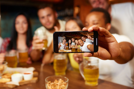 Group of funny friends taking self portrait in bar.