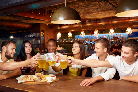 Smiling group of friends enjoying beer at pub, toasting and laughing. Standard-Bild