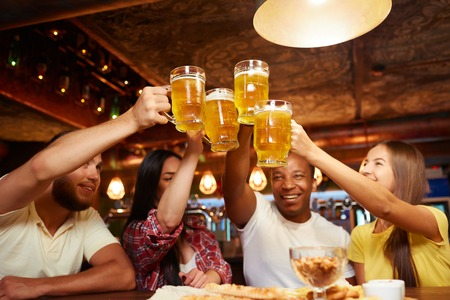 People raising beer glasses high above table and looking on drink.