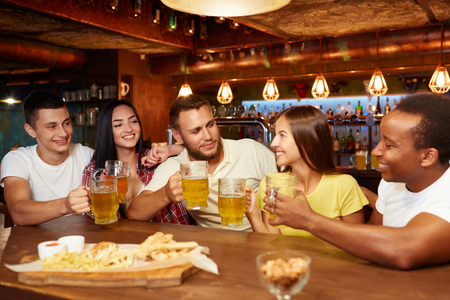 Company of happy friends sitting in bar at table with beer and snacks,. Фото со стока