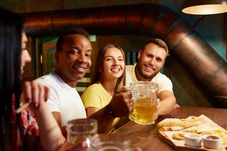 Company of happy friends sitting in bar drinking beer. Standard-Bild - 107927762