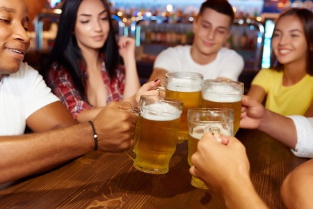 Group of happy friends enjoying beer at pub, toasting and laughing.