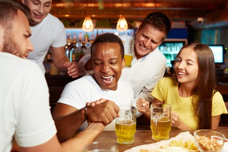 Excited male friends having arm wrestling challenge at local bar.