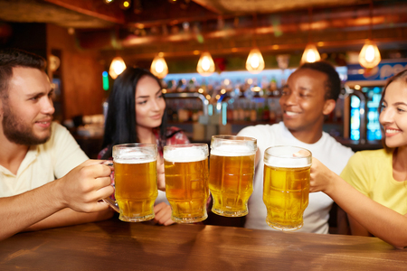 Four friends toasting with glasses of light beer at pub. Imagens