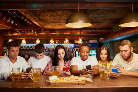 Group of six friends with serious facial expression, sitting with smartphones, drinking beer at bar. Фото со стока