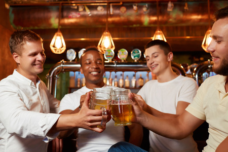 Four friends raising glasses of beer and celebrating their friendship in cozy pub.