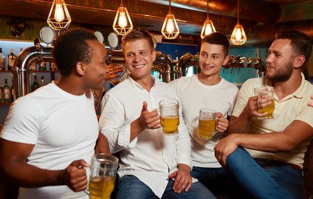 Company of four cheerful men enjoying light beer in stylish pub.