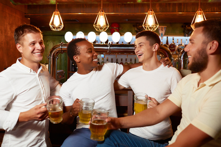 Company of four handsome men holding glass of beer, smiling and embracing.