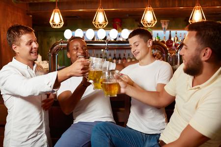 Four handsome men drinking beer together at pub clinking glasses.