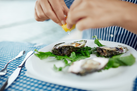 Womens hands squeezing lemon juice on raw oyster, close up Banco de Imagens