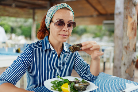 Young woman eating oyster in an outdoor restaurant Standard-Bild - 122913411
