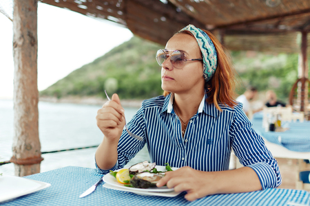 Young woman eating oyster in an outdoor restaurant Фото со стока