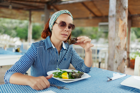 Young woman eating oyster in an outdoor restaurant Standard-Bild - 122913415