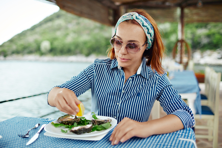 Woman eating a delicacy oyster, close-up outdoor restaurant Standard-Bild - 122913416